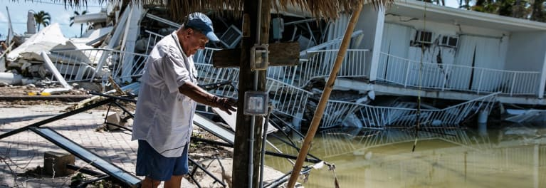 A man assesses the damage to his property after a storm
