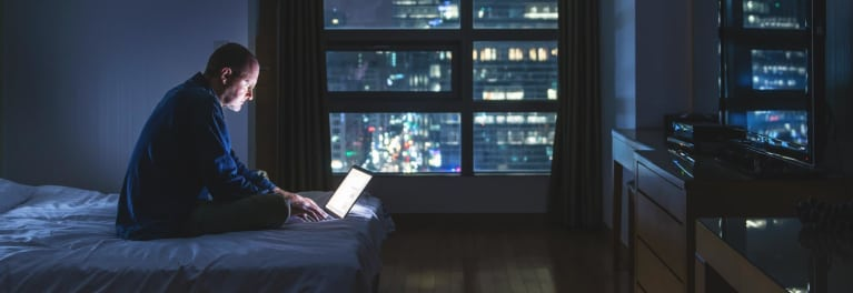Man in darkened hotel room on a laptop.
