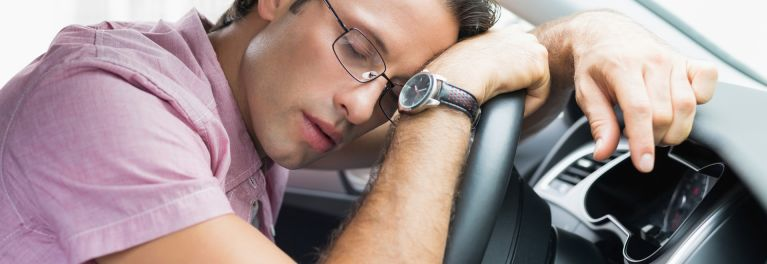 Man asleep at the wheel of a car