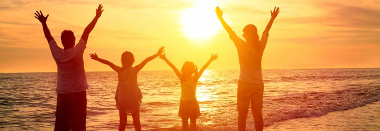 An image of adults and children having fun while silhouetted by the sun on the beach