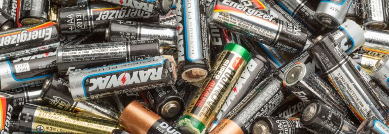 A pile of leaking AA batteries with potassium carbonate crust on their shells