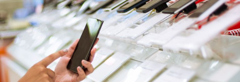 Photo of a someone tapping the blank screen of an unidentifiable smartphone in a store. In the blurry background, you can see a banko of dozens of other phones.