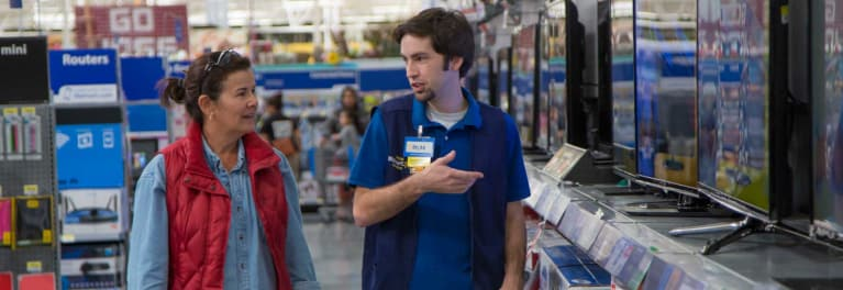 A Walmart employee talking with a customer.