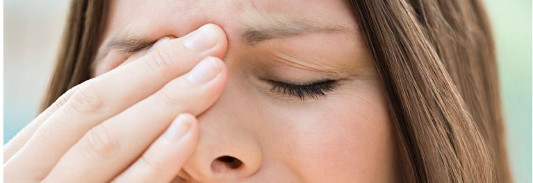 Antibiotics for sinus infections. Image of woman holding nose in pain.