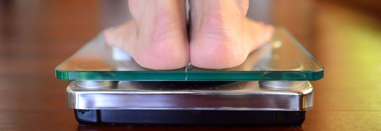 Feet on a clear scale to illustrate best time to weigh yourself.