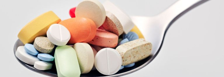 A spoon full of mixed dietary supplements, vitamins, and medications.