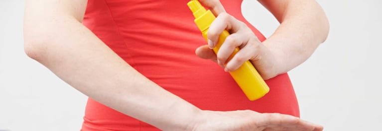 An image of a pregnant woman spraying herself with insect repellent.