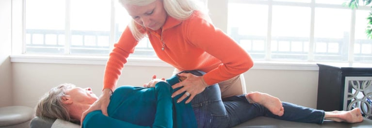 Woman getting treated by a chiropractor for back pain.