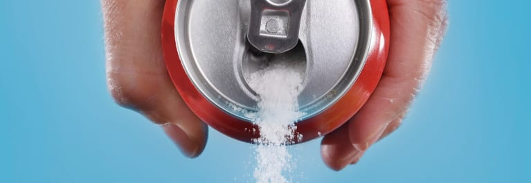 A sugary drink with sugar pouring out of the can.