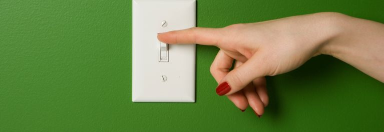 A woman turning off the lights to save on the electric bill.