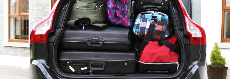 A car packed with hard-sided and soft-sided luggage.