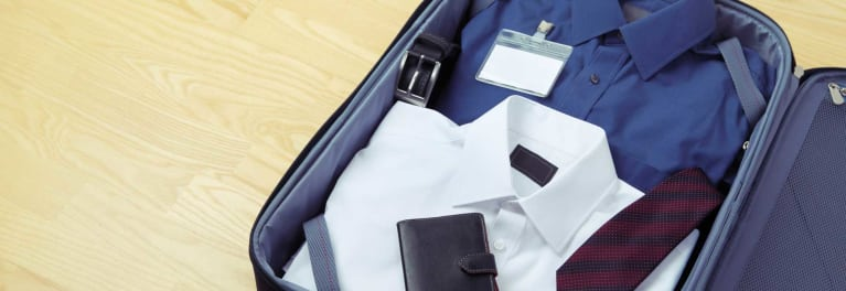 Shirts, a tie, a belt, a wallet, and an ID card inside luggage.