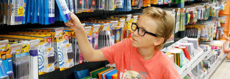 A child looking at back-to-school supplies in a store.