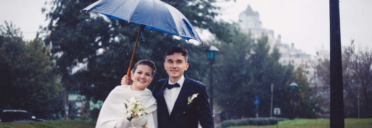 A bride and groom standing under an umbrella in the rain