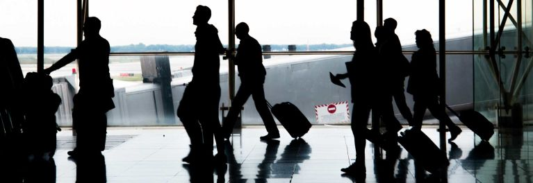 Silhouettes of people at an airport.