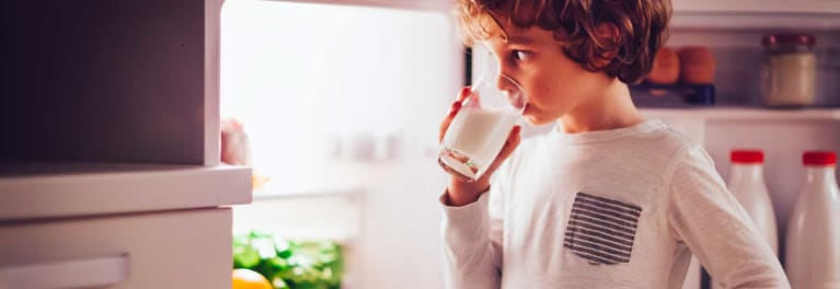A photo of a boy drinking a glass of milk