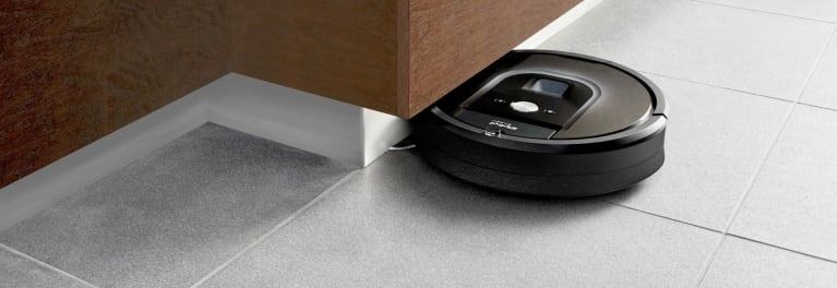 A Roomba vacuum cleaner on a tile floor