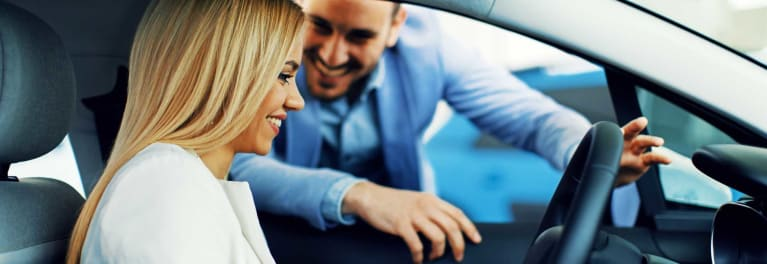 Best Used Cars by Price: A salesperson showing a woman a car.