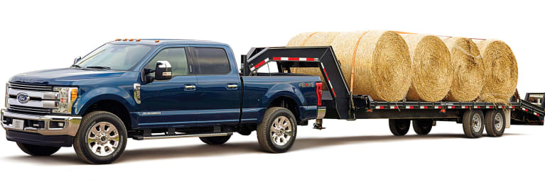 A heavy-duty Ford pickup truck towing large bales of hay.