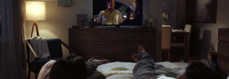 Photo of a person in bed watching Netflix on a TV.