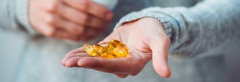 A hand holding fish oil supplements
