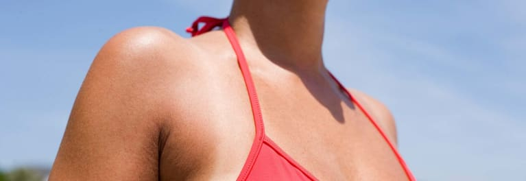 This photo shows a woman in a red bikini; summer skin care includes sunburn prevention.