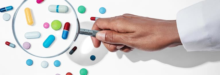 Magnifying glass enlarging pills on a table.