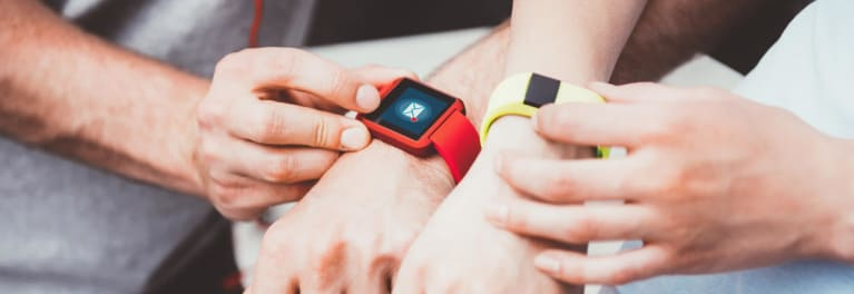 The arms of a young couple wearing fitness trackers.