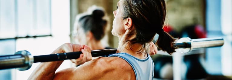 A woman lifting weights to maintain strong bones.