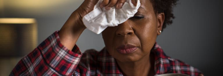A woman suffering from the flu who might need emergency flu treatment.