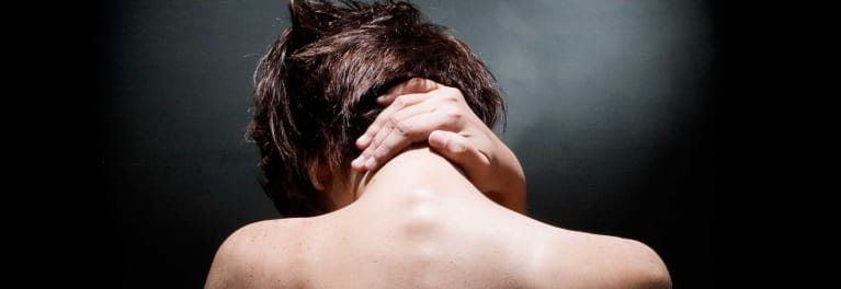 An image of someone massaging the back of their neck to relieve pain.