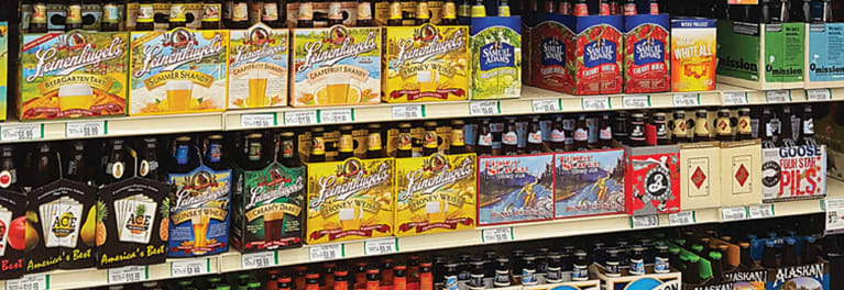 A photo of a grocery store shelf stocked with beer and ale.
