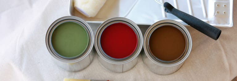 Three cans of interior paint plus a roller and paint pan.
