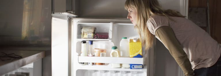 Woman looking in the fridge for a snack because sleep deprivation may lead to weight gain by increasing endocannabinoids.