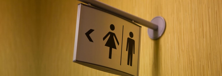 This is a picture of a sign pointing to the men's and women's bathrooms.