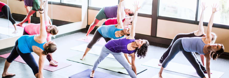 Women in a yoga class doing muscle building exercises.