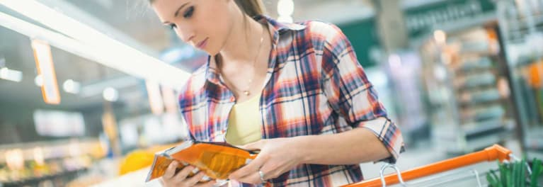Woman at the supermarket checking the nutrition facts label on a meat package.