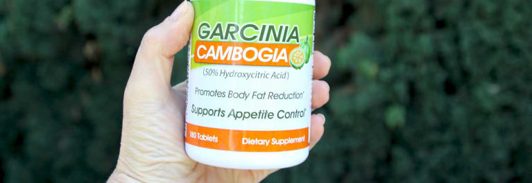 A hand holding a bottle of garcinia cambogia