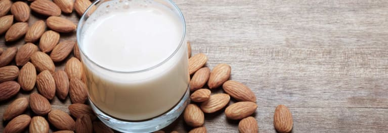 A glass of milk surrounded by almonds.