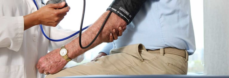 Photo of man getting blood pressure measured. High blood pressure is part of metabolic syndrome.