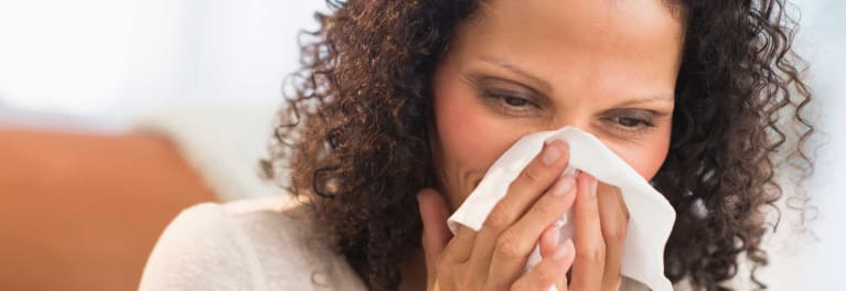 Photo of a woman sneezing for an article about how to fight bad allergies.