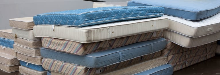 An old mattress on top of a stack of others.