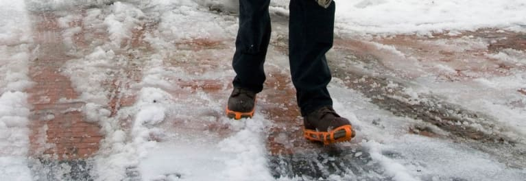 Someone clearing snow wearing ice cleats.