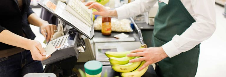 A shopper pays the cashier with a cash-back credit card to save at the supermarket.
