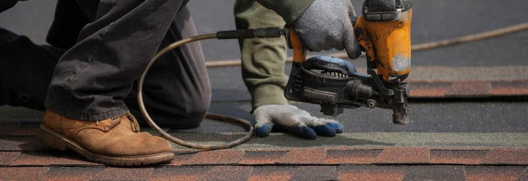 A roofing contractor on the job, working on the roof of a house.