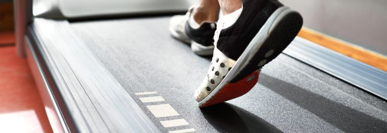 Feet of someone walking on a treadmill.