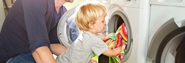 Child loading a front-load washer.