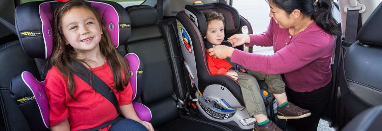 Two children sitting in car seats and a woman adjusting a car-seat strap.
