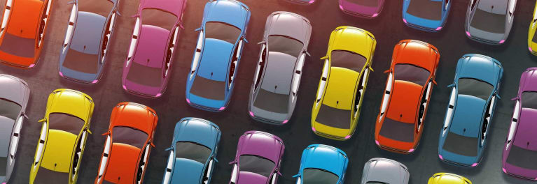 An overhead photo of many different colored vehicles in a new car dealership lot.