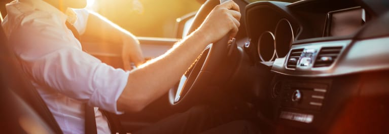 How to Get the Best Car Lease - A photo of a driver behind the steering wheel of a car.